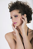 Portrait of a pretty woman with dramatic make up, touching her face Royalty Free Stock Image