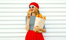 Portrait pretty woman eating croissant wearing red beret holding. Paper bag with long white bread baguette on white wall background royalty free stock photography
