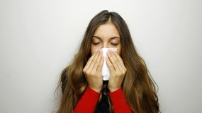 Portrait of a pretty woman having flu. girl blowing nose standing over gray background stock photos
