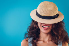 Portrait of a pretty woman hiding under hat and showing tongue. On blue background Stock Images