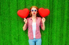 Portrait pretty woman holds red an air balloons in the shape of heart. Portrait pretty woman holds red an air balloons in the shape of a heart lies on the grass Royalty Free Stock Photo