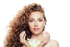 Portrait of pretty woman with long curly hair, clear skin and lily flower in her hands isolated on white background stock images