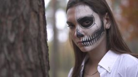 Portrait of a pretty woman with looking out from behind a tree with the skull makeup on the face shows big cleaver and. Portrait of a pretty woman with looking stock video
