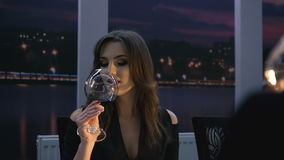Portrait of pretty woman raises and toastes wine glasses in restaurant in 4K stock footage