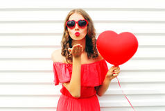 Portrait pretty woman in red dress sends air kiss with balloon heart shape over white. Background Royalty Free Stock Photo