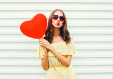 Portrait pretty woman with red lips sends kiss with air balloon heart shape over white. Background Stock Photography
