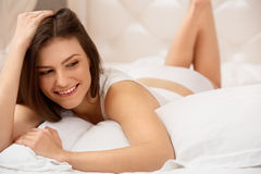 Portrait of a pretty woman relaxing in bed Royalty Free Stock Photo