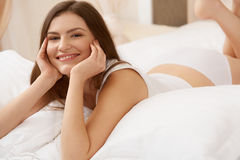 Portrait of a pretty woman relaxing in bed Stock Image
