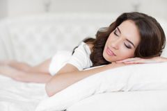 Portrait of a pretty woman relaxing in bed Stock Photography