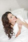 Portrait of a pretty woman relaxing in bed Stock Images