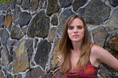 Portrait of a pretty woman by a rock wall. Portrait of a pretty woman leaning against a wall Stock Images