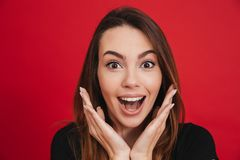 Portrait of pretty woman 20s holding arms at face and smiling br. Oadly isolated over red background Royalty Free Stock Photos