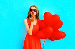 Portrait pretty woman sends air kiss with balloons on blue. Portrait pretty woman sends an air kiss with a balloons on blue background Stock Photos