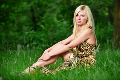 Portrait of a pretty woman sitting in the grass Royalty Free Stock Photos