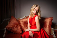 Portrait of pretty woman sitting in red dress Stock Photography