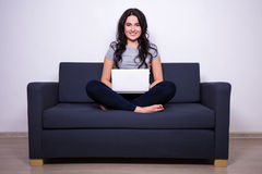 Portrait of pretty woman sitting on sofa and using laptop at hom Royalty Free Stock Photo