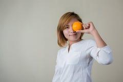 Portrait of pretty woman smile holding orange fruit Stock Photos