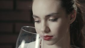 Portrait pretty woman sniffing wineglass and drinking red wine close up stock video
