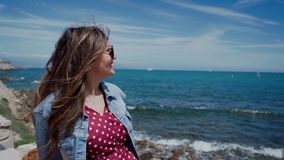 Portrait of pretty woman in sunglasses sitting by the sea and enjoying sunny day and amazing sea view. 4k stock video