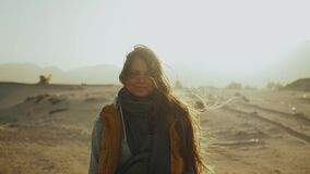 Portrait of pretty woman on sunset. Happy young woman standing in wind against a desert sunset landscape, slow motion.