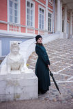 Portrait of a pretty woman in vintage autumn clothes. Full-length portrait of a pretty woman in vintage autumn clothes standing in front of old city buildings Stock Photography