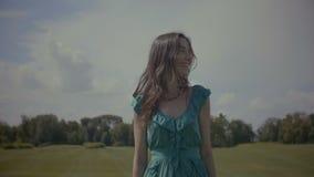Portrait of pretty woman walking in green field
