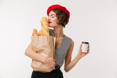 Portrait of a pretty woman wearing beret smelling. Paper bag with long loaf while holding cup of coffee isolated over white background Stock Images