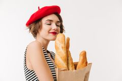 Portrait of a pretty woman wearing beret smelling. Paper bag with long loaf isolated over white background Stock Photo