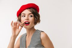Portrait of a pretty woman wearing red beret. Eating cookies isolated over white background Stock Photos