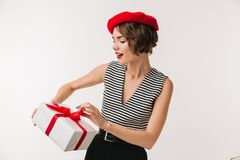 Portrait of a pretty woman wearing red beret. Holding present box isolated over white background Stock Images