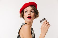 Portrait of a pretty woman wearing red beret. Holding cup of coffee and looking away isolated over white background Royalty Free Stock Image