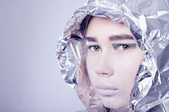 Portrait of pretty woman wrapped in foil looking Stock Photography