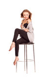 Portrait of pretty women in studio, sitting on a bar chair in un Royalty Free Stock Photos