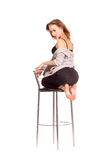 Portrait of pretty women in studio, sitting on a bar chair in un Royalty Free Stock Image