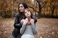 Portrait of pretty woman and teen girl. They are posing in autumn park. Beautiful landscape at fall season royalty free stock photography