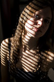 Portrait of pretty women under sun. Beautiful woman home under blind-light royalty free stock photography