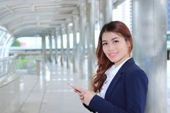Portrait of pretty young Asian business woman holding mobile smart phone and looking on camera at walkway with copy space backgrou stock image