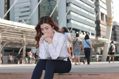 Portrait of pretty young Asian business woman thinking and sitting on stairway in urban building background. Portrait of pretty young Asian business woman Royalty Free Stock Photography
