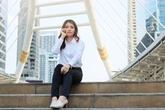 Portrait of pretty young Asian woman sitting and talking on phone at urban city background. royalty free stock photos