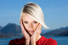 Pretty young blond woman. Portrait of pretty young blond woman with head in hands, sea or lake in background Stock Photo