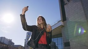 Portrait of the pretty young blonde girl taking selfie photos on the smartphone device camera while walking urban street stock video