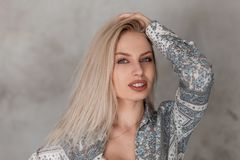 Portrait of a pretty young blonde woman with blue eyes with plump sexy lips in a fashionable gray summer shirt with a pattern