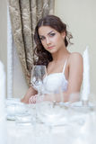 Portrait of pretty young brunette sitting at table Royalty Free Stock Photos