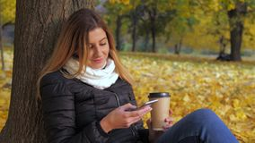 Woman Sitting With Her Back To The Tree In Yellow Autumn Leaves, Uses Smartphone. Portrait pretty young brunette woman sitting with her back to the tree on the stock footage