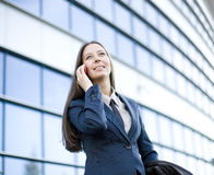 Portrait of pretty young business woman talking on phone near building. Talking Royalty Free Stock Images