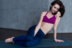 Portrait of pretty young Caucasian yogini wearing sportswear sitting on floor looking at camera Stock Photos
