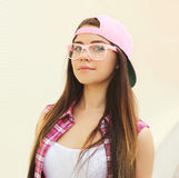 Portrait of pretty young cool girl wearing a pink clothes. And glasses outdoors Stock Image