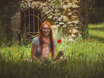 Portrait of pretty, young, cute woman in glasses sitting on green meadow with poppy flower, Pompeii, Italy Royalty Free Stock Photo