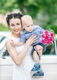 Portrait of pretty young female bride walking, holding baby boy with wedding roses bouquet and looking into camera at sunny summer. Park. Mother and her little Royalty Free Stock Photography