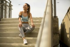 Young female runner resting on the stairs. Portrait of pretty young female runner resting on the stairs Royalty Free Stock Photography